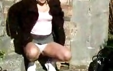 Curly girl pissing on the street