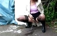Pissing woman in a white coat