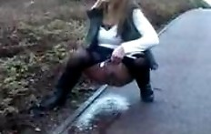 Woman pissing on the sidewalk